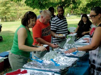 Past President Gwynn Roberson serves the feast